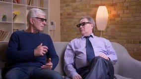 Παλαιοί αρσενικοί φίλοι στα τρισδιάστατα γυαλιά που προσέχουν τον κινηματογράφο μαζί στη TV και που συζητούν ενθουσιωδώς απόθεμα βίντεο