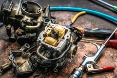 Παλαιοί εξαερωτήρας και εργαλεία μοτοσικλετών στο σκουριασμένο πίνακα στοκ φωτογραφίες