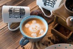 Παλαιοί μύλος καφέ και φλυτζάνι καφέ με τα διεσπαρμένα φασόλια και τα μπισκότα καφέ στο ξύλινο υπόβαθρο Στοκ Φωτογραφία