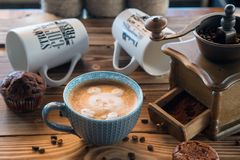 Παλαιοί μύλος καφέ και φλυτζάνι καφέ με τα διεσπαρμένα φασόλια και τα μπισκότα καφέ στο ξύλινο υπόβαθρο Στοκ εικόνες με δικαίωμα ελεύθερης χρήσης