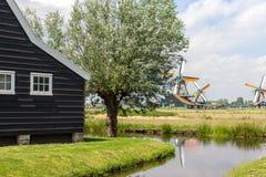 Παλαιοί ολλανδικοί ανεμόμυλοι, λίμνη και ξύλινο σπίτι στο ιστορικό χωριό Μύλοι της Ολλανδίας στον τομέα με τον ποταμό και το αρχα στοκ φωτογραφία