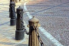 Παλαιοί στυλοβάτες σιδήρου με την αλυσίδα στο πεζοδρόμιο κοντά στο δρόμο Στοκ εικόνα με δικαίωμα ελεύθερης χρήσης