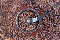 Παλαιός αναδρομικός μύλος καφέ με τα ψημένα φασόλια καφέ και το υπόβαθρο καφέ Στοκ Εικόνες
