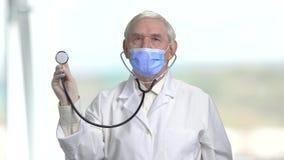 Παλαιός ανώτερος γιατρός στο στηθοσκόπιο εκμετάλλευσης μασκών απόθεμα βίντεο