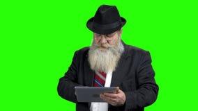 Παλαιός γενειοφόρος επιχειρηματίας που χρησιμοποιεί την ψηφιακή ταμπλέτα απόθεμα βίντεο