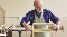 Παλαιός γκρίζος μαλλιαρός ξυλουργός με το moustache και γενειάδα που μετρά το ξύλινο σπίτι κουκλών απόθεμα βίντεο