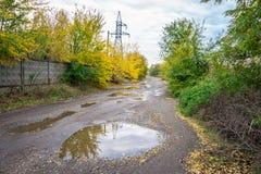Παλαιός δρόμος με τις λακκούβες στη βιομηχανική περιοχή το φθινόπωρο Στοκ εικόνες με δικαίωμα ελεύθερης χρήσης