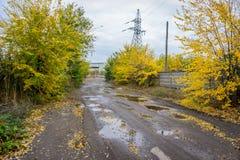 Παλαιός δρόμος με τις λακκούβες στη βιομηχανική περιοχή το φθινόπωρο Στοκ Εικόνες