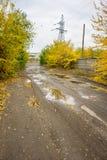 Παλαιός δρόμος με τις λακκούβες στη βιομηχανική περιοχή το φθινόπωρο Στοκ φωτογραφίες με δικαίωμα ελεύθερης χρήσης