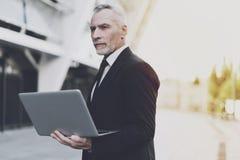 Παλαιός επιχειρηματίας που εργάζεται στο lap-top στην οδό Στοκ Εικόνες