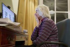 Παλαιός ηλικιωμένος ανώτερος υπολογιστής εκμάθησης προσώπων και σε απευθείας σύνδεση απάτη απάτης χρημάτων δεξιοτήτων Διαδικτύου  στοκ εικόνα