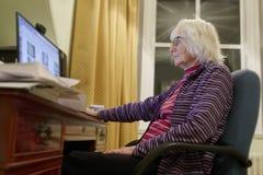 Παλαιός ηλικιωμένος ανώτερος υπολογιστής εκμάθησης προσώπων και σε απευθείας σύνδεση απάτη απάτης χρημάτων δεξιοτήτων Διαδικτύου  στοκ εικόνες