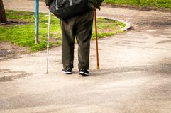Παλαιός καταθλιπτικός περίπατος ατόμων μόνο κάτω από την οδό με τη μόνη και χαμένη άποψη συναισθήματος ραβδιών ή καλάμων περπατήμ Στοκ Εικόνες