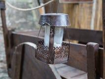 Παλαιός κρεμασμένος σίδηρος λαμπτήρας, ξύλινο καφετί κάρρο στο υπόβαθρο Στοκ Εικόνες