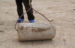 Παλαιός κύλινδρος πετρών χρήσεων ατόμων για να συμπιέσει την επίπεδη στέγη της γης στοκ φωτογραφίες με δικαίωμα ελεύθερης χρήσης