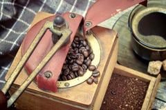 Παλαιός μύλος καφέ με ένα φλιτζάνι του καφέ Στοκ Εικόνες