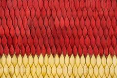 Παλαιός ξεπερασμένος ξύλινος τοίχος με τη διακόσμηση που χρωματίζεται στο κόκκινο και κίτρινη Στοκ εικόνα με δικαίωμα ελεύθερης χρήσης