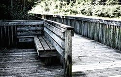 Παλαιός ξύλινος πάγκος σε μια γέφυρα κοντά σε έναν δρόμο το καλοκαίρι Γκρίζα εικόνα στοκ εικόνες