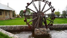 Παλαιός ξύλινος υδρόμυλος στο ναυπηγείο χωρών Μικρή ξύλινη περιστροφή υδρομύλων σε μια μικρή λίμνη, διακόσμηση στον κήπο στοκ φωτογραφία με δικαίωμα ελεύθερης χρήσης