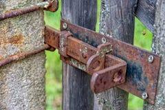 Παλαιός οξυδωμένος σύρτης που εξασφαλίζει κλείσιμο της ξύλινης πύλης Στοκ Εικόνες