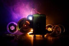 Παλαιός προβολέας κινηματογράφων ύφους, κινηματογράφηση σε πρώτο πλάνο Προβολέας ταινιών σε ένα ξύλινο υπόβαθρο με το δραματικό φ Στοκ Εικόνα
