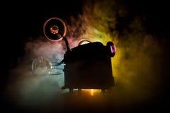 Παλαιός προβολέας κινηματογράφων ύφους, κινηματογράφηση σε πρώτο πλάνο Προβολέας ταινιών σε ένα ξύλινο υπόβαθρο με το δραματικό φ Στοκ Εικόνες