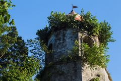Παλαιός πύργος εκκλησιών στον πράσινο θάμνο Ισπανικός πύργος θόλων στο μπλε ουρανό Στοκ Εικόνα