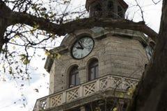 Παλαιός πύργος ρολογιών πόλεων σε ένα νεφελώδες υπόβαθρο ουρανού Στοκ Εικόνες