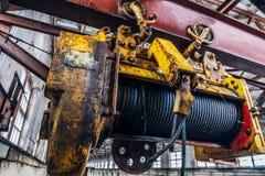 Παλαιός σκουριασμένος ανελκυστήρας του βιομηχανικού υπερυψωμένου γερανού στο εργοστάσιο κλείστε επάνω στοκ εικόνα