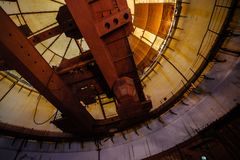 Παλαιός σκουριασμένος βιομηχανικός πολικός περιστροφικός γερανός του τύπου γεφυρών κάτω από το θόλο της εγκαταλειμμένης κατασκευή Στοκ Εικόνες