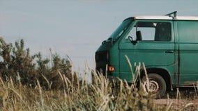 Παλαιός σκουριασμένος πράσινος minivan που σταθμεύουν στο βρώμικο δρόμο, ξηρά χλόη απόθεμα βίντεο