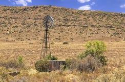 Παλαιός σπασμένος ανεμόμυλος που στέκεται αχρησιμοποίητος με τα δέντρα και τους Μπους αγκαθιών που αυξάνονται από τη δεξαμενή στοκ φωτογραφίες με δικαίωμα ελεύθερης χρήσης