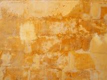 Παλαιός στενοχωρημένος επιδιορθωμένος κίτρινος τοίχος πετρών που χρωματίζεται στις διαφορετικές σκιές του εξασθενισμένου λεκιασμέ στοκ φωτογραφίες με δικαίωμα ελεύθερης χρήσης