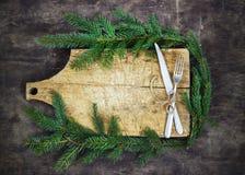 Παλαιός τέμνων πίνακας με τους κομψούς κλάδους σε ένα ξύλινο υπόβαθρο με τα Χριστούγεννα μαγειρέματος κουζινών δικράνων και μαχαι Στοκ φωτογραφία με δικαίωμα ελεύθερης χρήσης