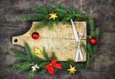 Παλαιός τέμνων πίνακας με τους κομψούς κλάδους σε ένα ξύλινο υπόβαθρο με τα Χριστούγεννα μαγειρέματος κουζινών δικράνων και μαχαι Στοκ φωτογραφίες με δικαίωμα ελεύθερης χρήσης