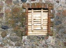 Παλαιός τοίχος πετρών τα κόκκινα τούβλα που πλαισιώνονται με που επιβιβάζονται επάνω στο παράθυρο Στοκ φωτογραφία με δικαίωμα ελεύθερης χρήσης