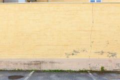 Παλαιός φορεμένος κίτρινος συμπαγής τοίχος υπαίθρια στοκ εικόνες