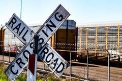 Παλαιός φορεμένος σιδηρόδρομος που διασχίζει το σημάδι μπροστά από έναν οδοντωτό - φράκτης καλωδίων και αυτοκίνητα Στοκ φωτογραφία με δικαίωμα ελεύθερης χρήσης