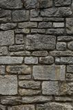 Παλαιός φυσικός τοίχος πετρών των γκρίζων και κιτρινωπών πετρών στα διαφορετικά μεγέθη ως υπόβαθρο στοκ φωτογραφία