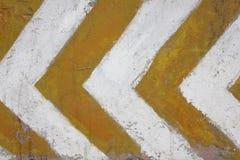 παλαιός χτυπημένος συμπαγής τοίχος με τα κίτρινα και άσπρα βέλη που δηλώνουν τον κίνδυνο r στοκ εικόνες