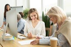 Παλαιότερη επιχειρηματίας που υπογράφει τη σύμβαση με το χαμογελώντας θηλυκό διευθυντή στοκ εικόνα με δικαίωμα ελεύθερης χρήσης