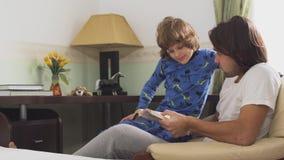 Παλαιότερος αδελφός που διαβάζει ένα βιβλίο στο μικρότερο αδερφό του Αδελφοί στις πυτζάμες που κάθονται σε μια καρέκλα που συζητά απόθεμα βίντεο