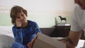Παλαιότερος αδελφός που διαβάζει τη συνεδρίαση βιβλίων ενός μικρότερου αδερφού στην άκρη του κρεβατιού στην κρεβατοκάμαρα το πρωί φιλμ μικρού μήκους