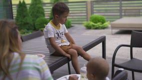 Παλαιότερος αδελφός που προσέχει: Νέα μητέρα που ταΐζει τη συνεδρίαση γιων αγοράκι της σε ένα κάθισμα παιδιών - θερμό καλοκαίρι χ απόθεμα βίντεο