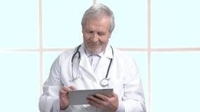 Παλαιότερος γιατρός που εργάζεται στην ταμπλέτα υπολογιστών απόθεμα βίντεο