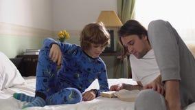 Παλαιότερος και μικρότεροι αδερφοί στις πυτζάμες που βρίσκονται στο κρεβάτι στην κρεβατοκάμαρα στο πρωί φιλμ μικρού μήκους