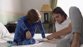 Παλαιότερος και μικρότεροι αδερφοί στις πυτζάμες που βρίσκονται στο κρεβάτι στην κρεβατοκάμαρα στο πρωί Οι αδελφοί διαβάζουν ένα  απόθεμα βίντεο
