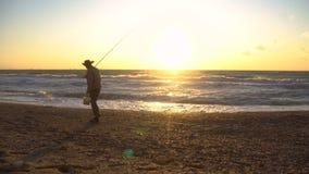 Παλαιότερος ψαράς στο καπέλο που αλιεύει στην ανατολή στην ακτή της θάλασσας στο θυελλώδη καιρό απόθεμα βίντεο
