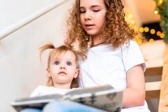 Παλαιότερο βιβλίο ανάγνωσης αδελφών μεγαλοφώνως στη νεώτερη αδελφή της στη σκάλα στοκ εικόνα