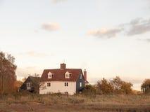 Παλαιό άσπρο εξοχικό σπίτι αγροτικών σπιτιών χωρών στον τομέα στοκ εικόνα